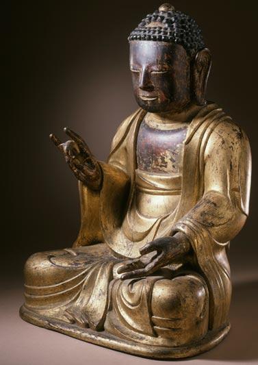 A seated Buddha making a karana mudrā hand gesture.